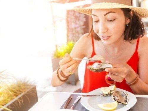 Donna che sta per degustare un'ostrica